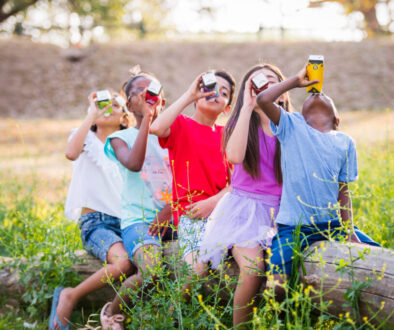Group of children sitting on a tree log and drinking from recyclable liquid board packaging